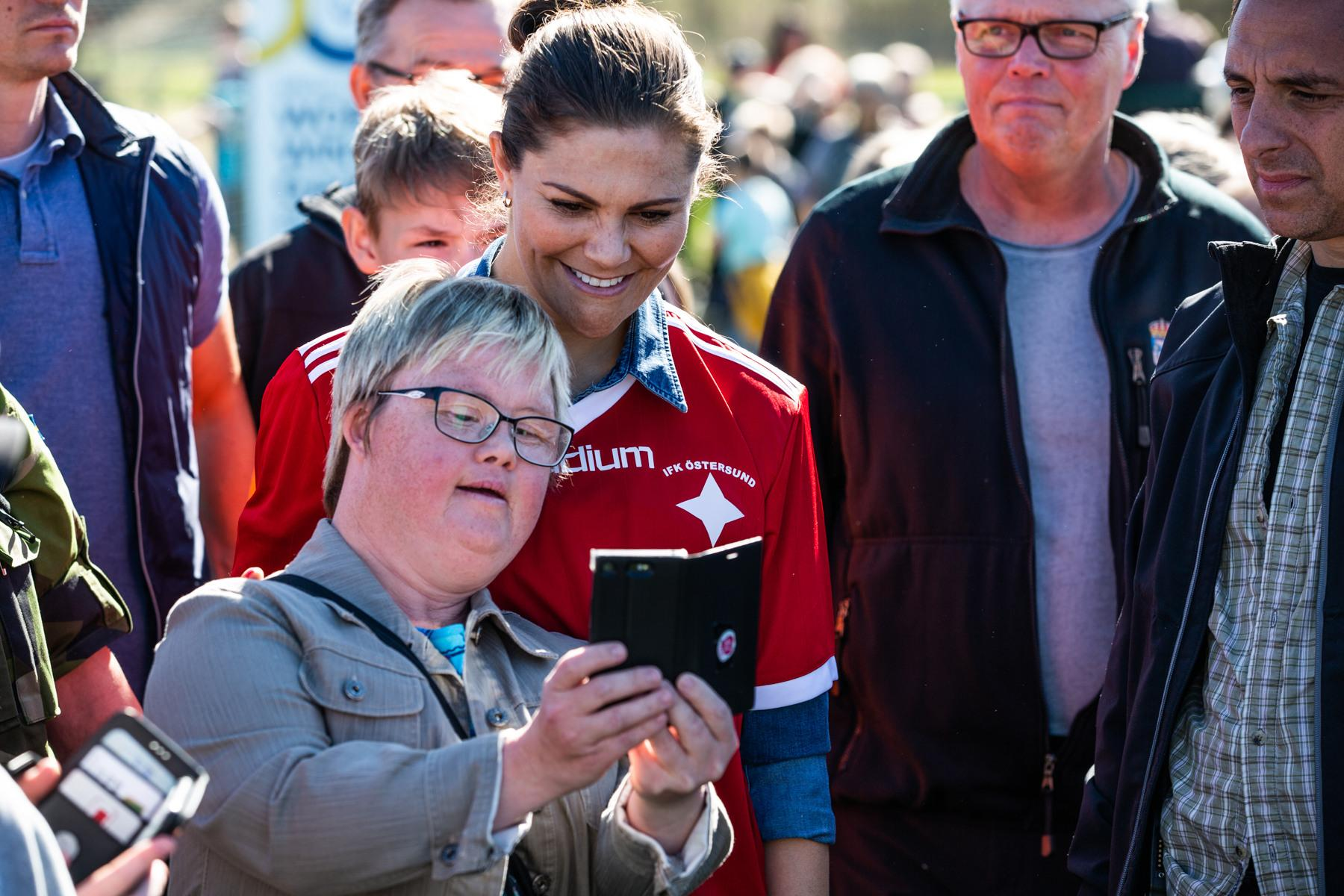 Crown Princess Victoria in a football T-shirt being shown something on a woman's mobile phone.