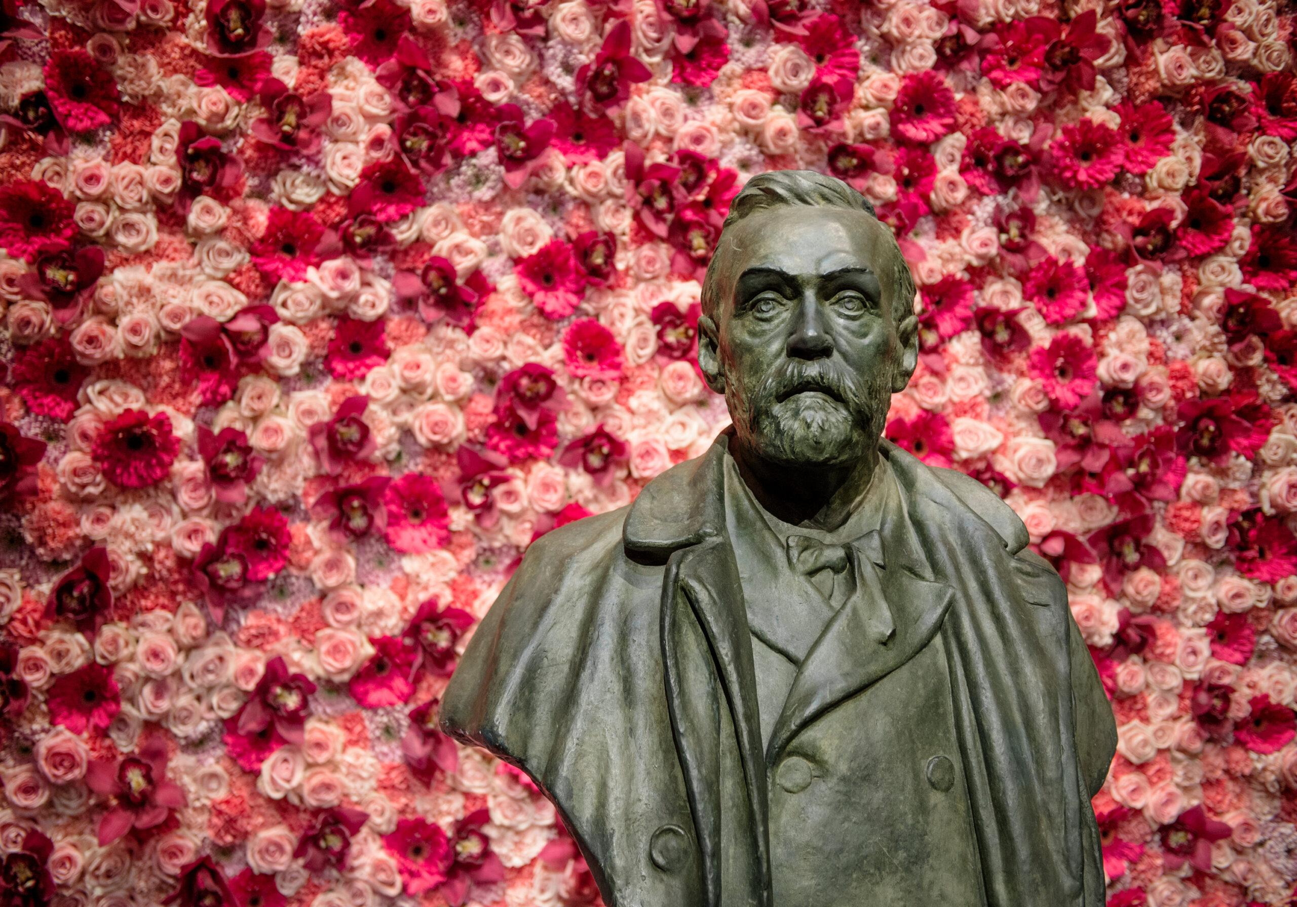 A bust of Alfred Nobel in front of a wall of flowers.