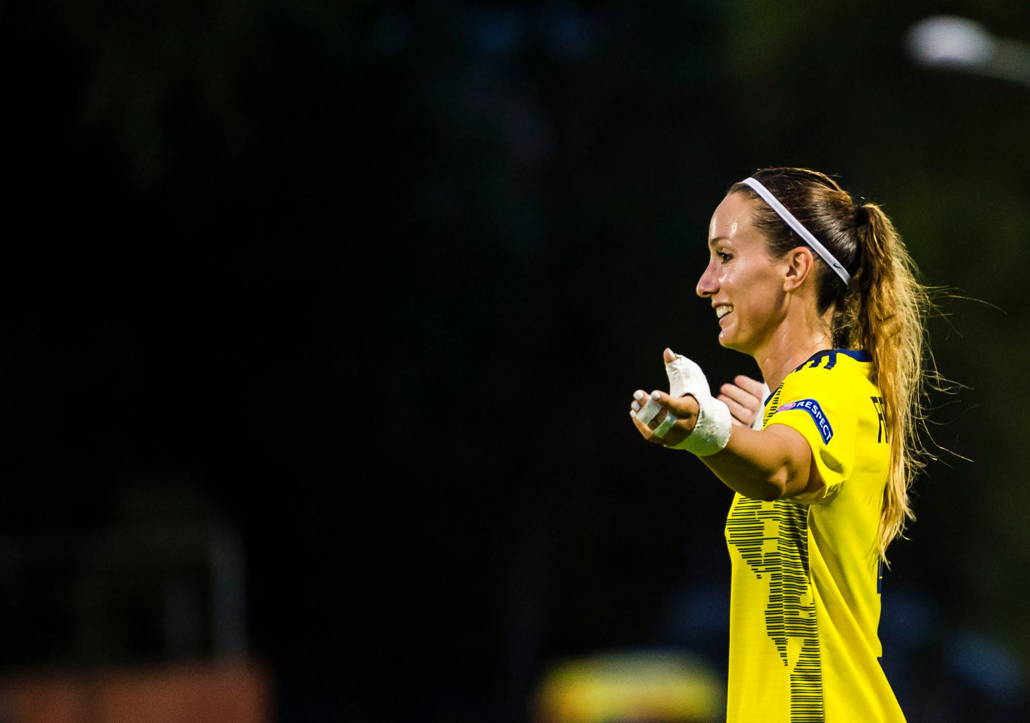 Kosovare Asllani in a yellow Sweden T-shirt with her arms out.