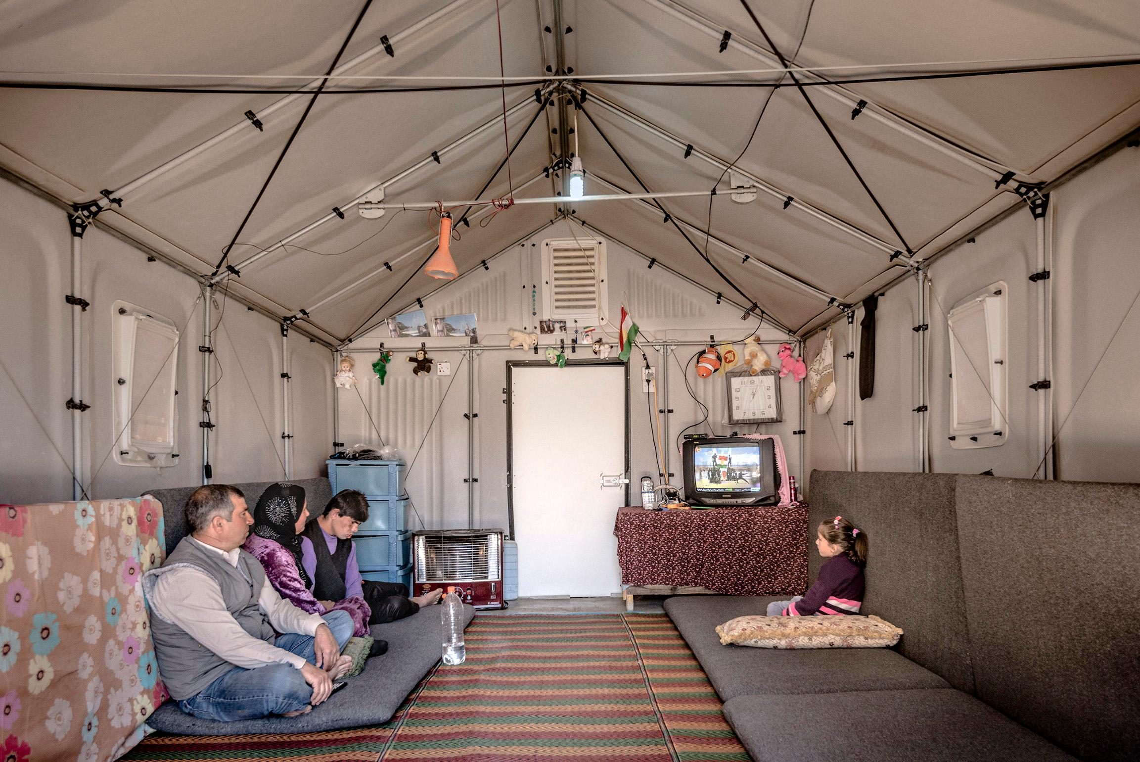 Two grown-ups and two children sitting on cushions on the floor in a tent with solid walls.