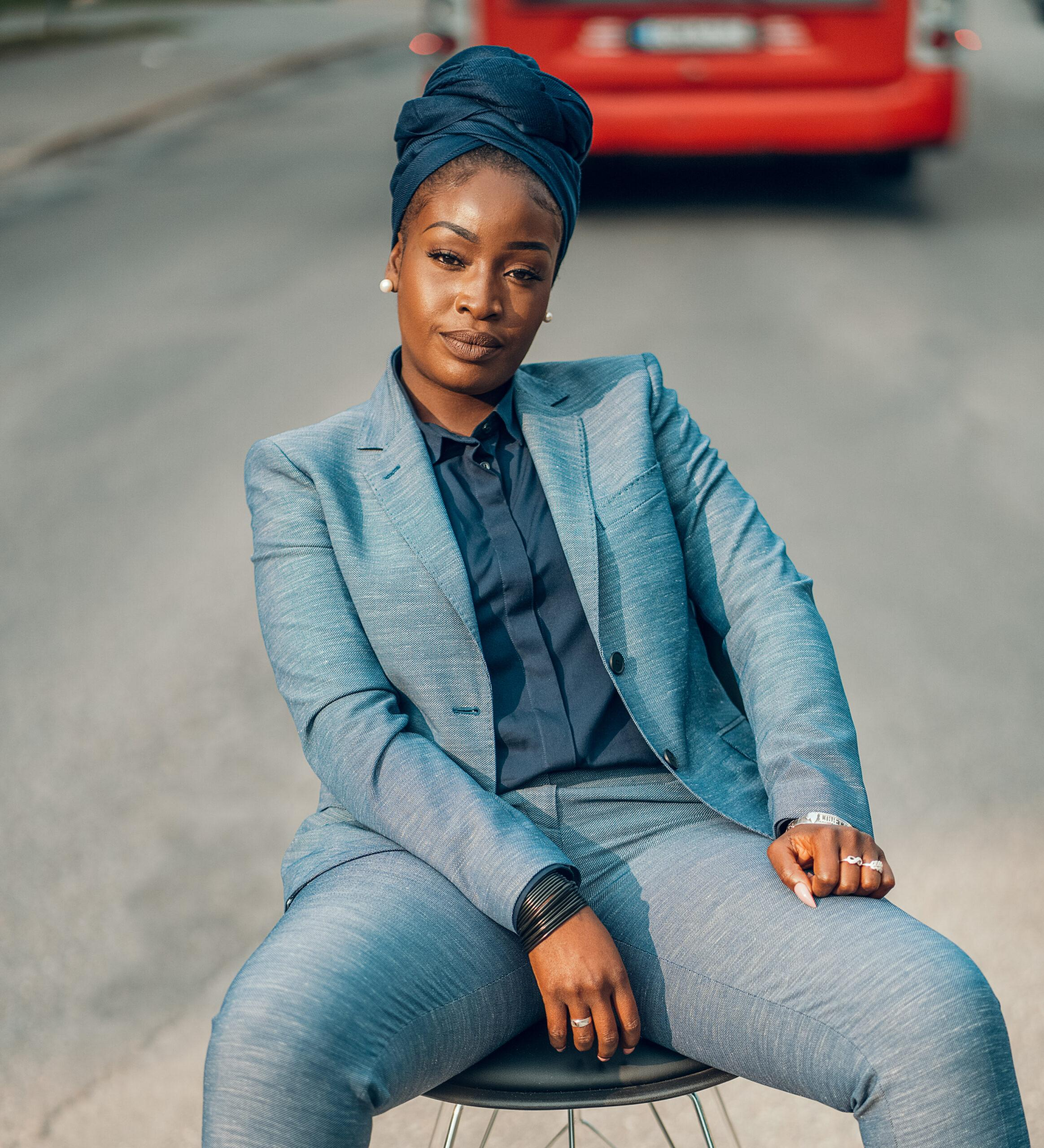 Portrait of Lovette Jallow in a blue suit and a scarf on her head sitting down looking straight into the camera.