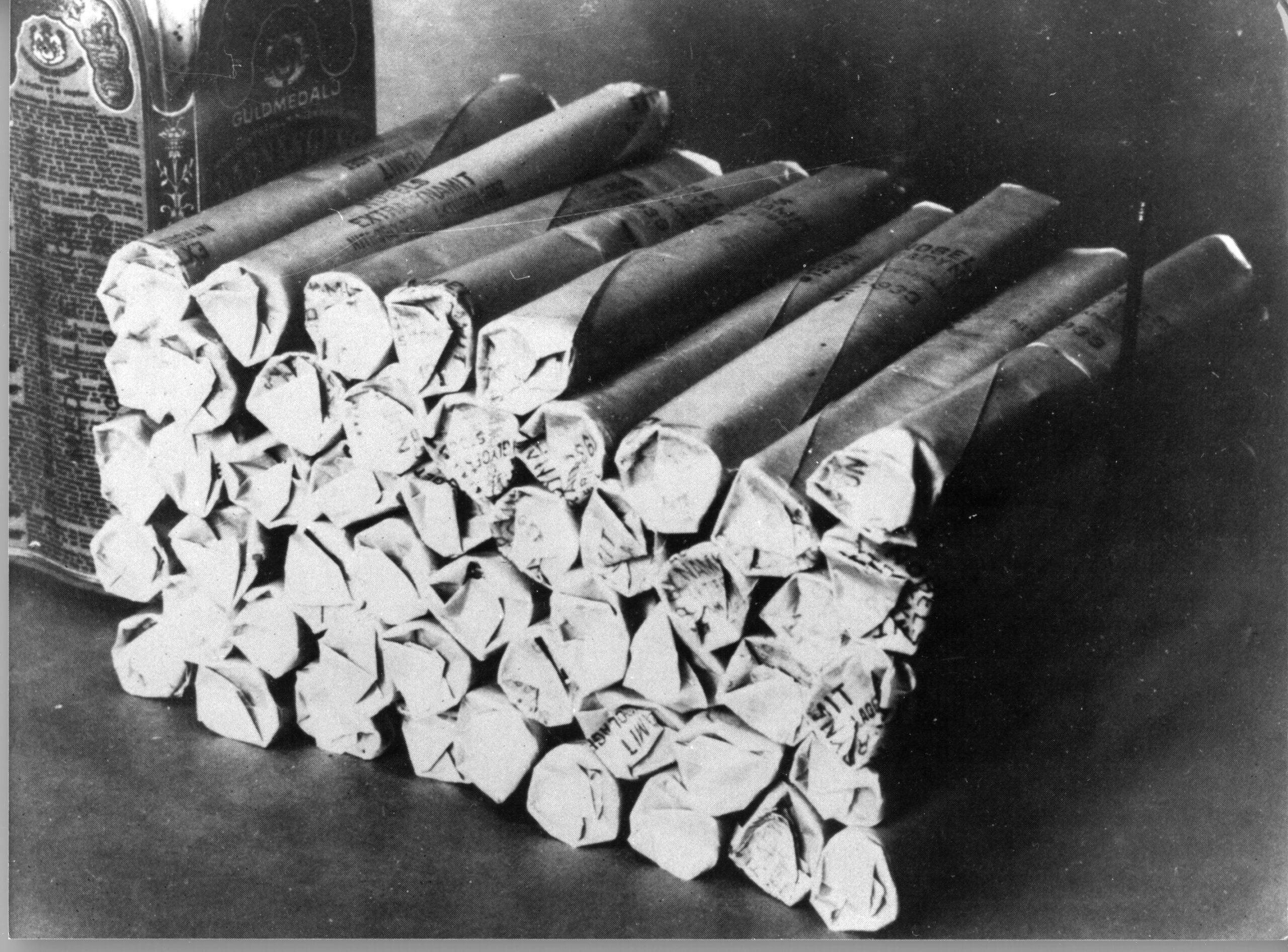A black-and-white photo of a pile of dynamite.