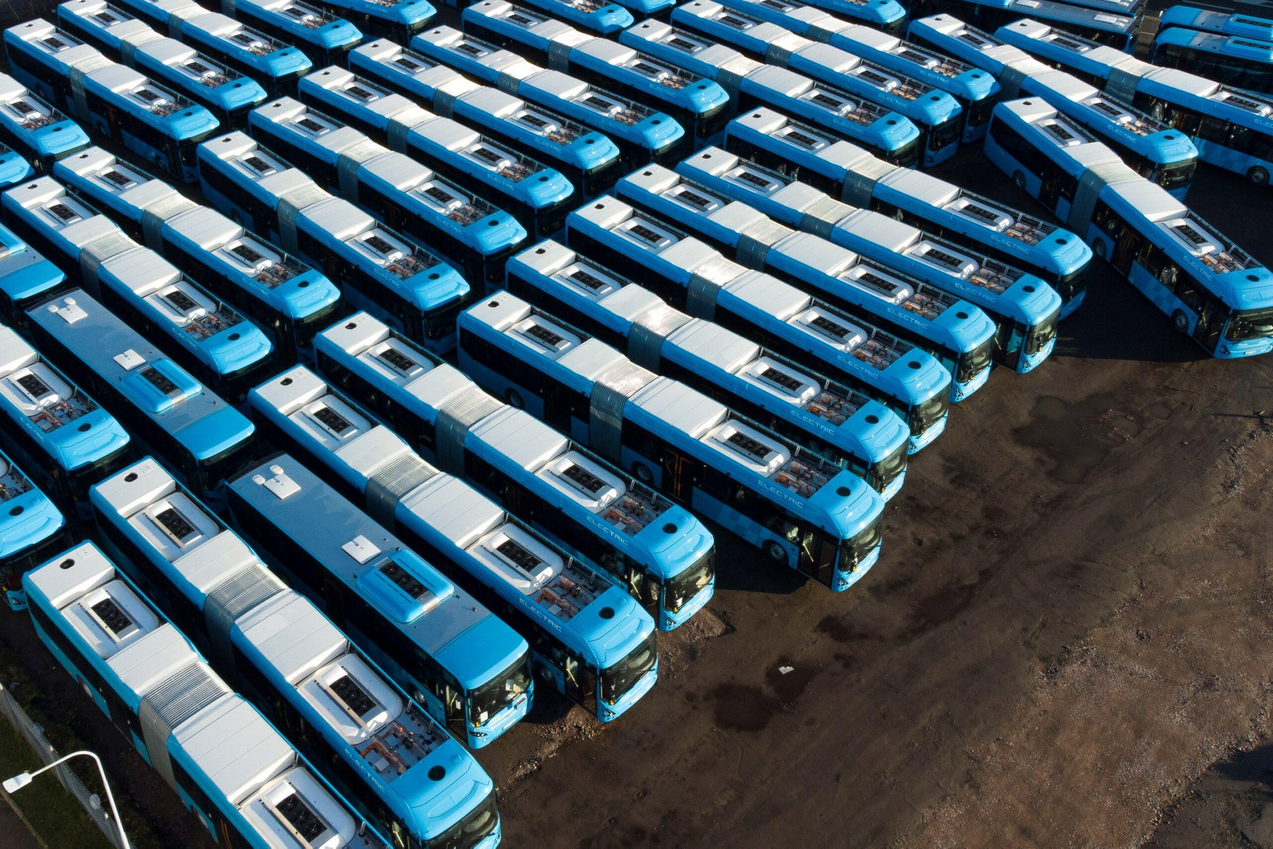 Aerial view of lots of buses parked close together.