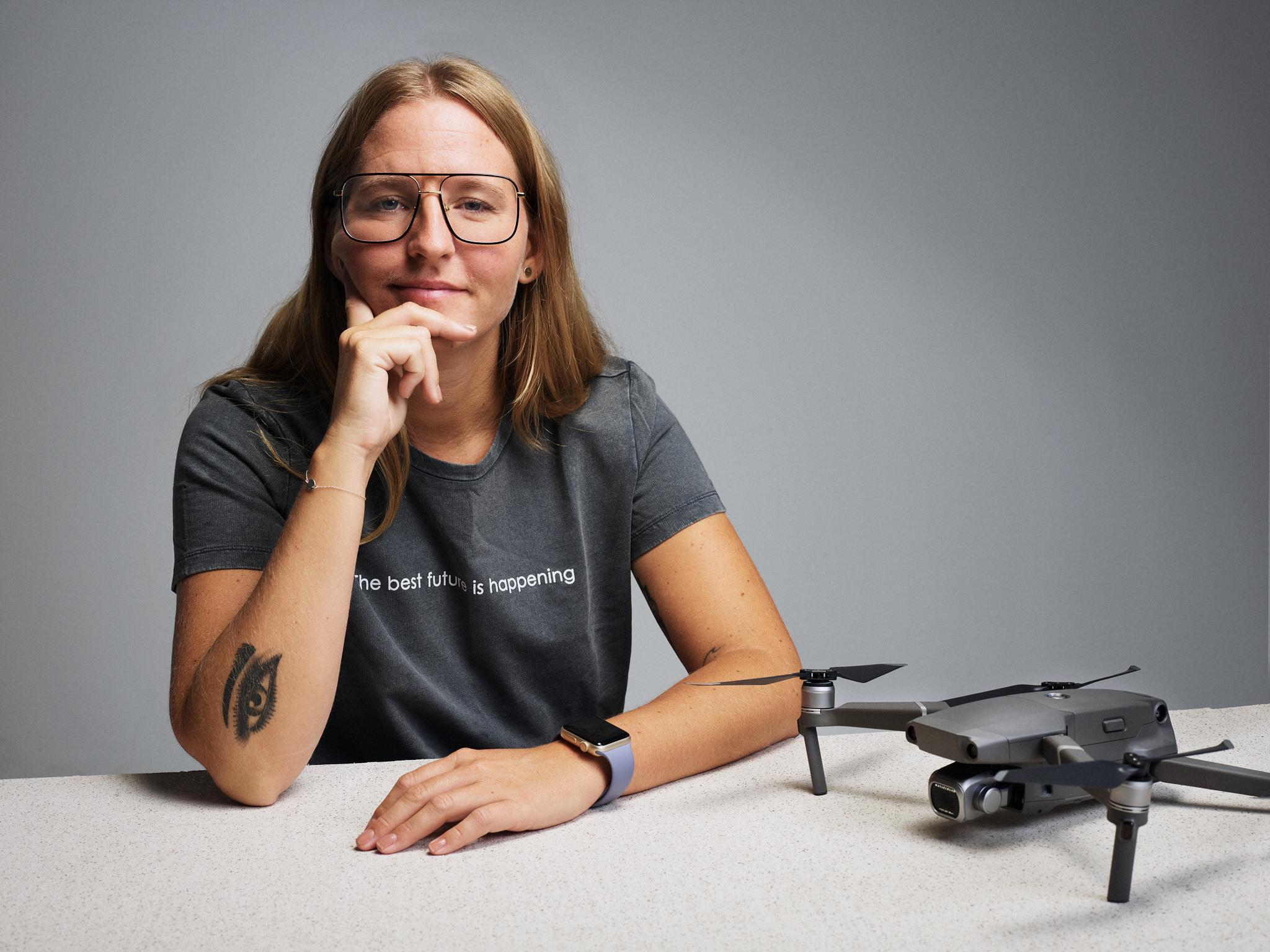 Portrait of Helena Samsioe with a drone on the table in front of her.