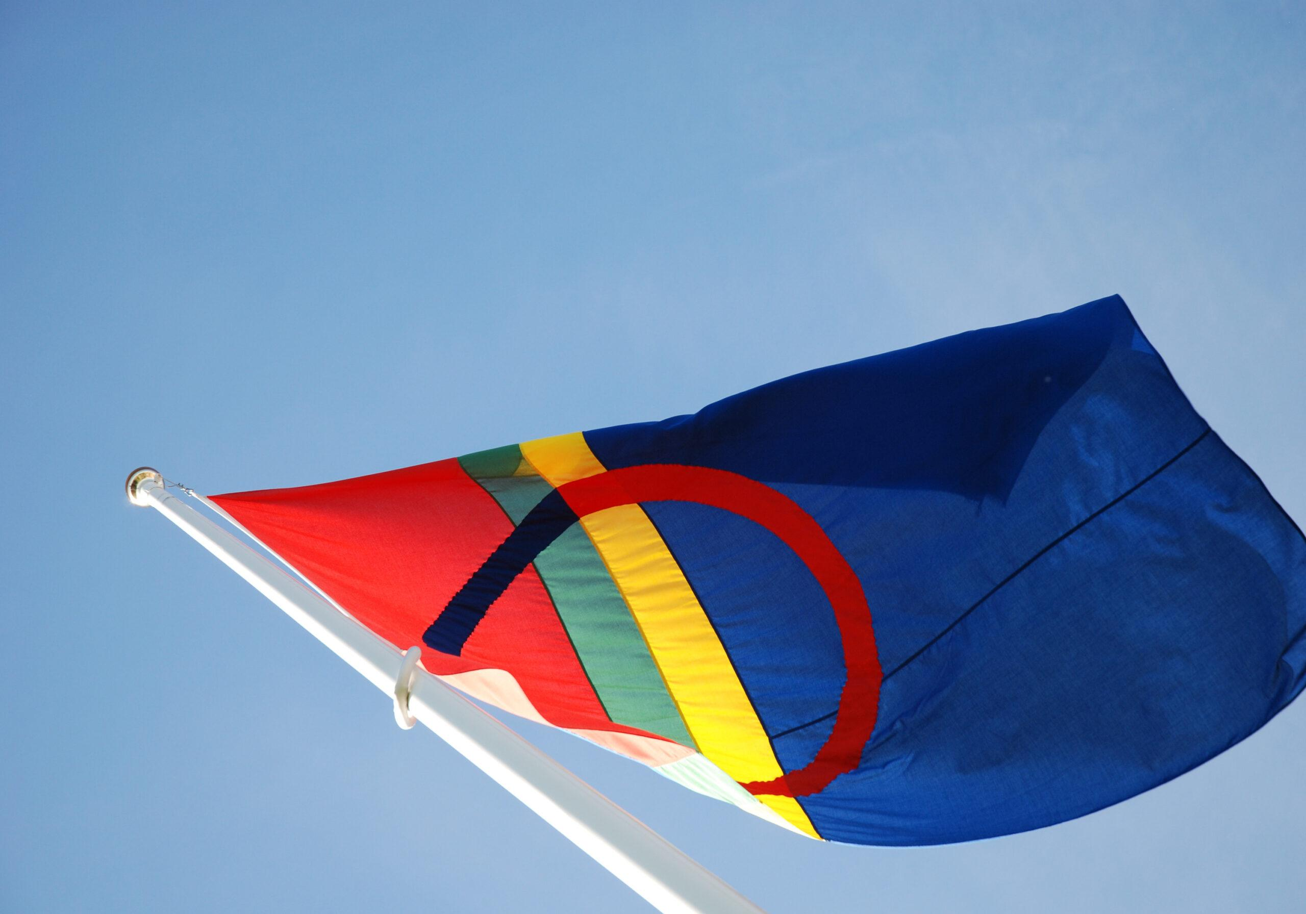 The Sami flag - red, blue, green and yellow – blowing in the wind.