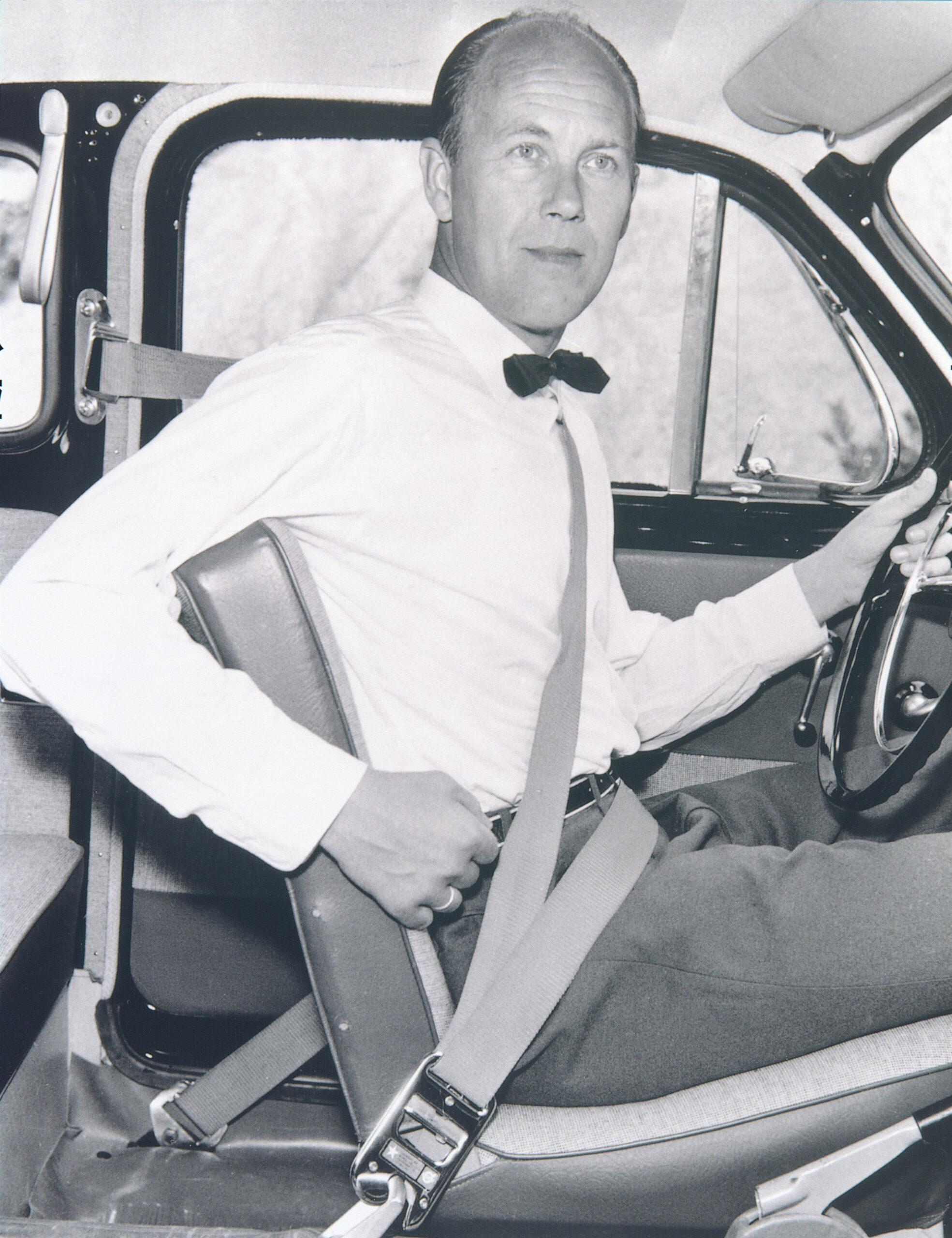 A black-and-white photo of a man in a car wearing a seatbelt.