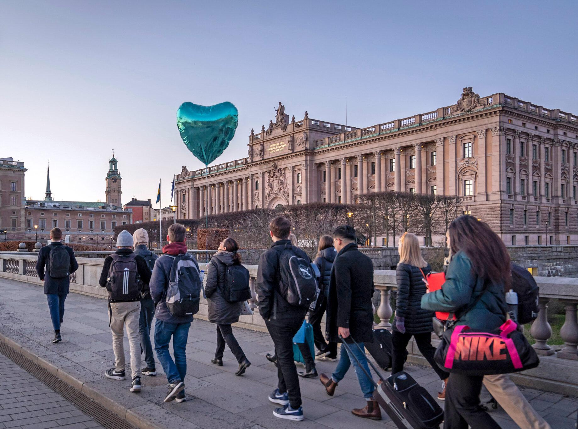 Young people walking outside the Swedish parliament building in Stockholm.