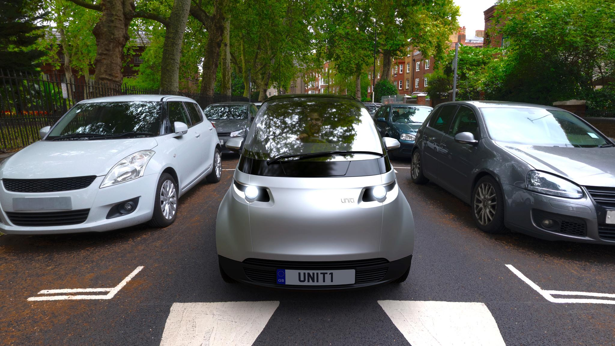 A futuristic-looking, silver-coloured car driving on the road between parked cars on each side.
