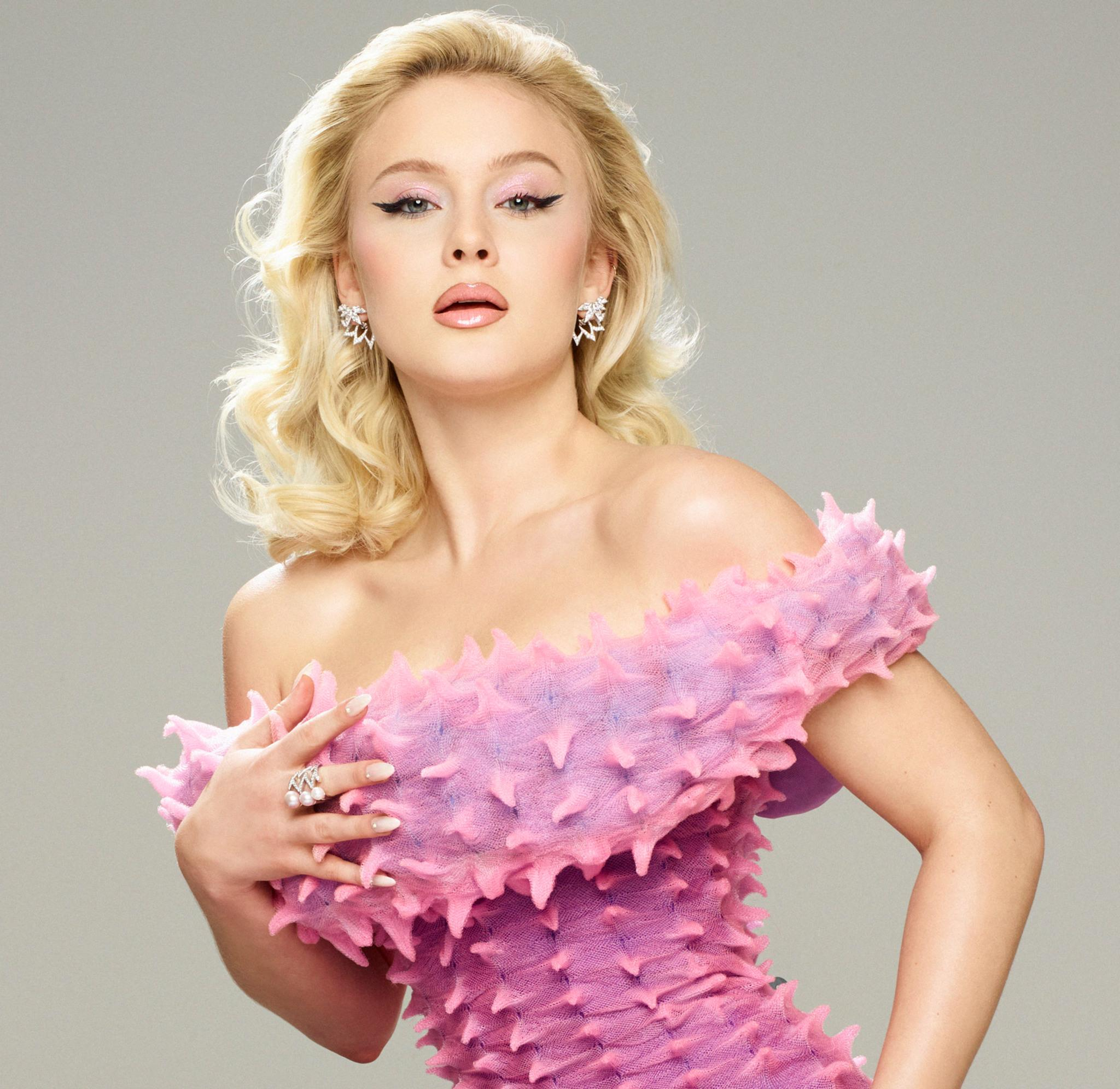 Portrait of Zara Larsson wearing a pink dress with a spike-like surface.
