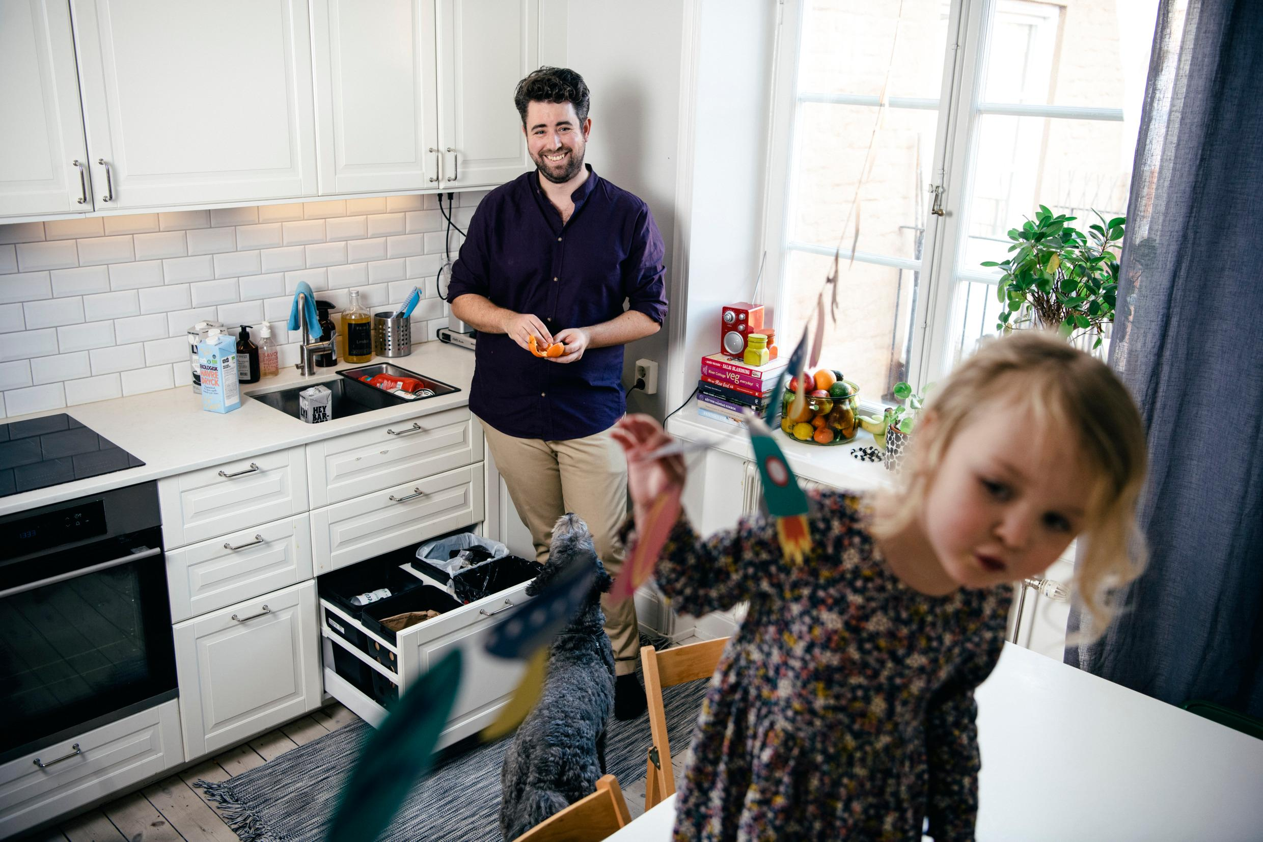 A father and his daughter in a kitchen by a drawer with recycling.