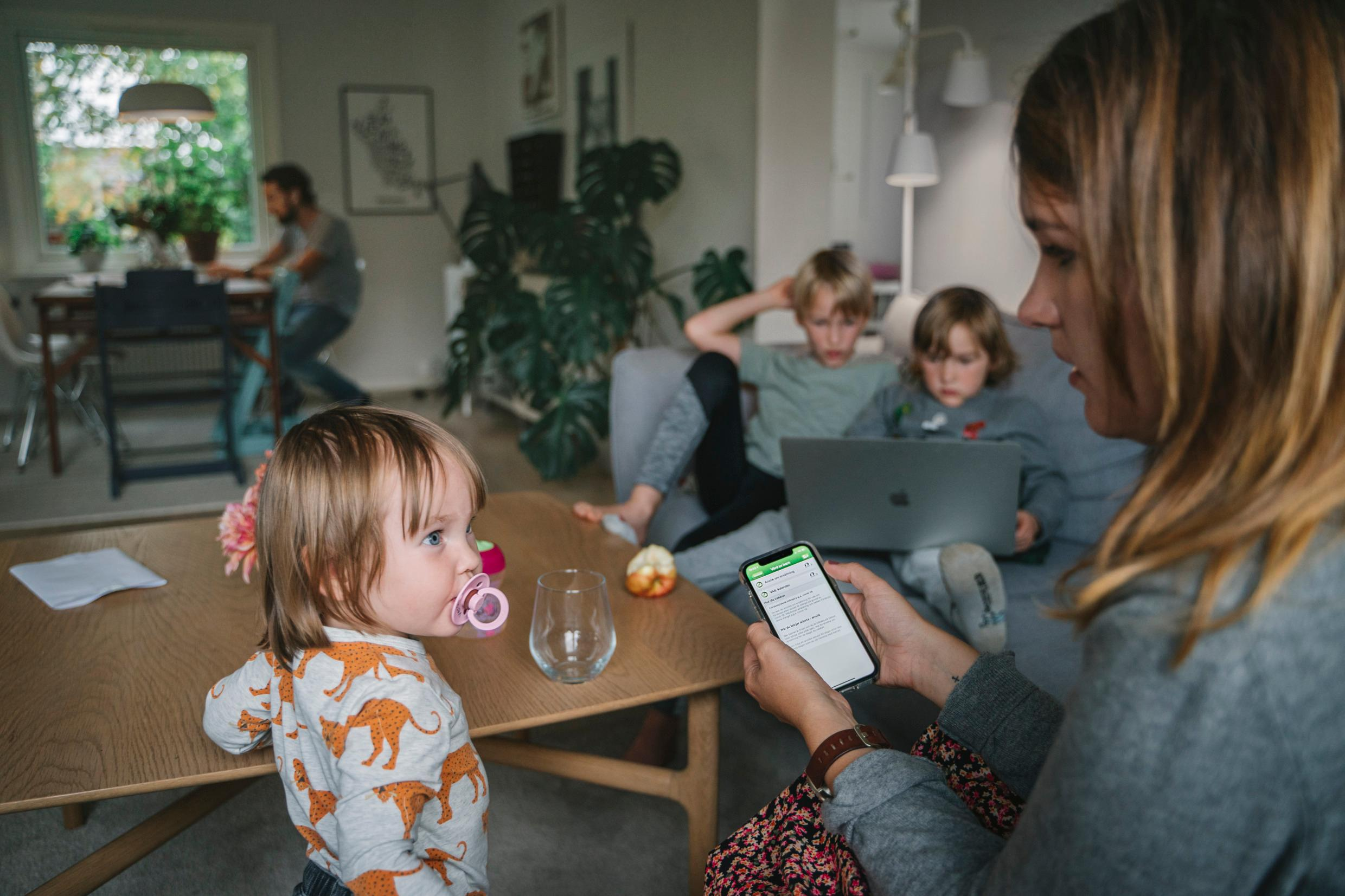 A family setting in a living room, with three children, a mother and a father. Two kids watch something on a laptop. The mother is using her phone.