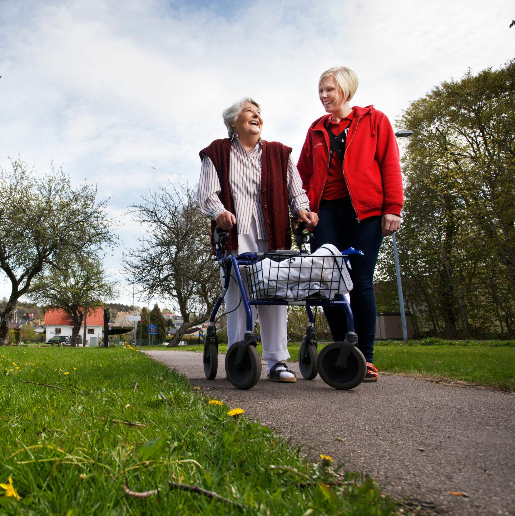 An elderly woman in a park walking with a walking frame together with a younger woman.