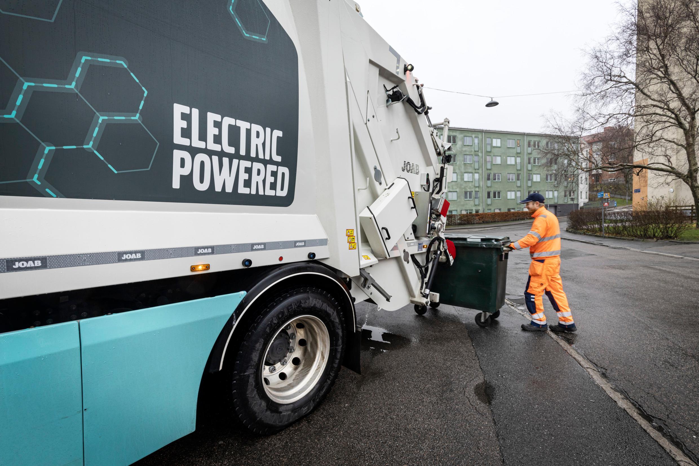 A man is pushing a waste bin toward a truck.
