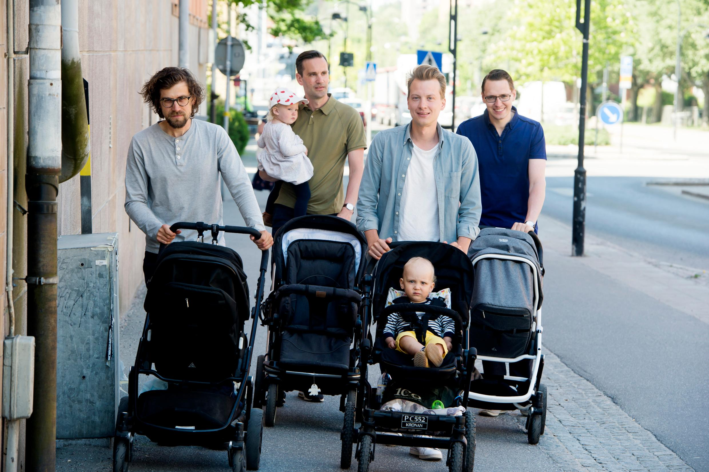 Four men with baby strollers walk down the street. Each man has a baby stroller.