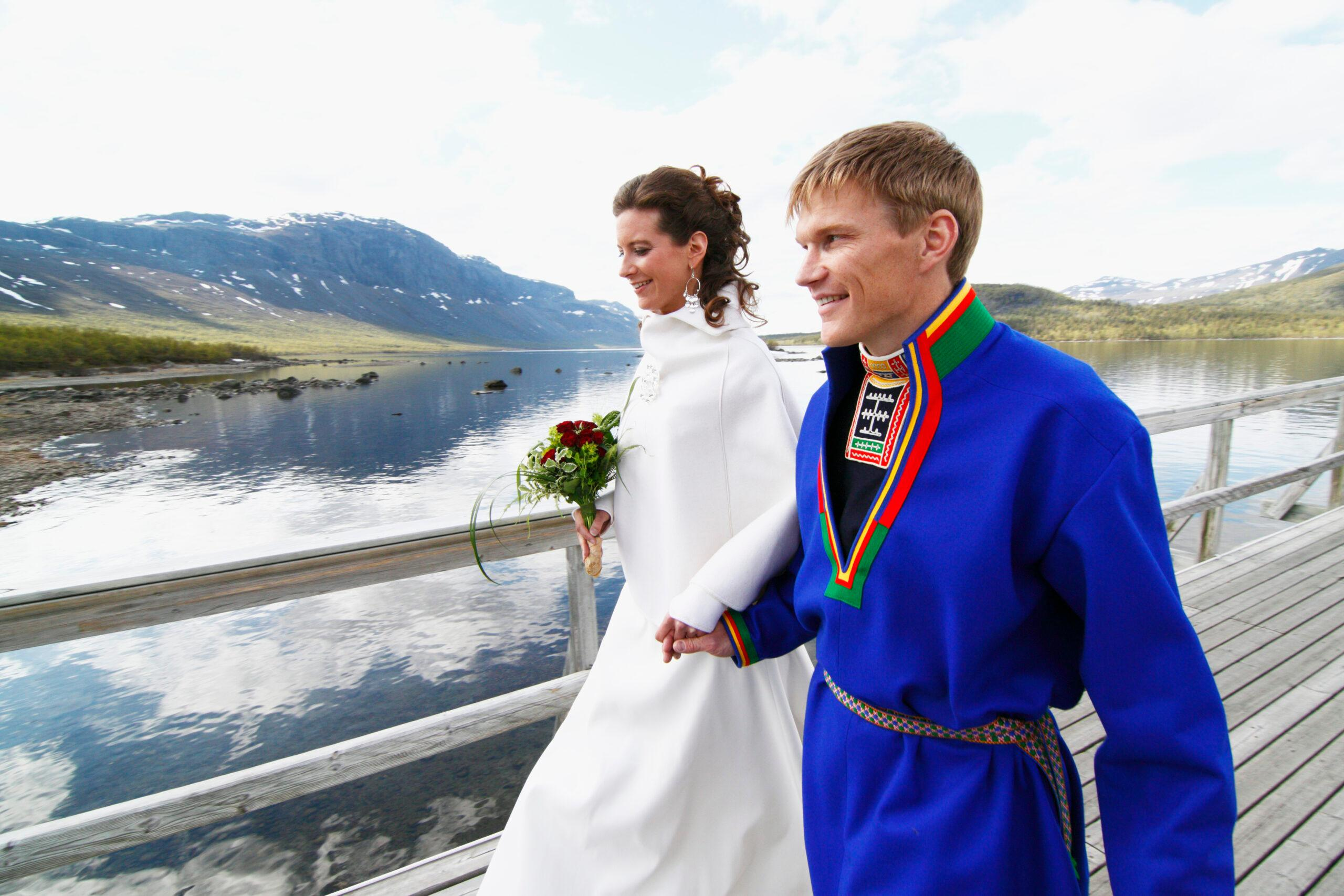 A newlywed couple - the woman in a white dress, the man in a traditional sami costume - walking across a bridge. Mountains in the background.