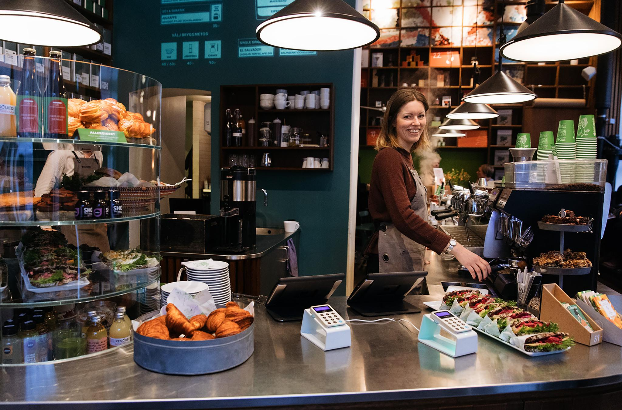 The counter of a café, with food and drink on the sides, machines for card payments on the counter and a woman looking into the camera behind the counter.