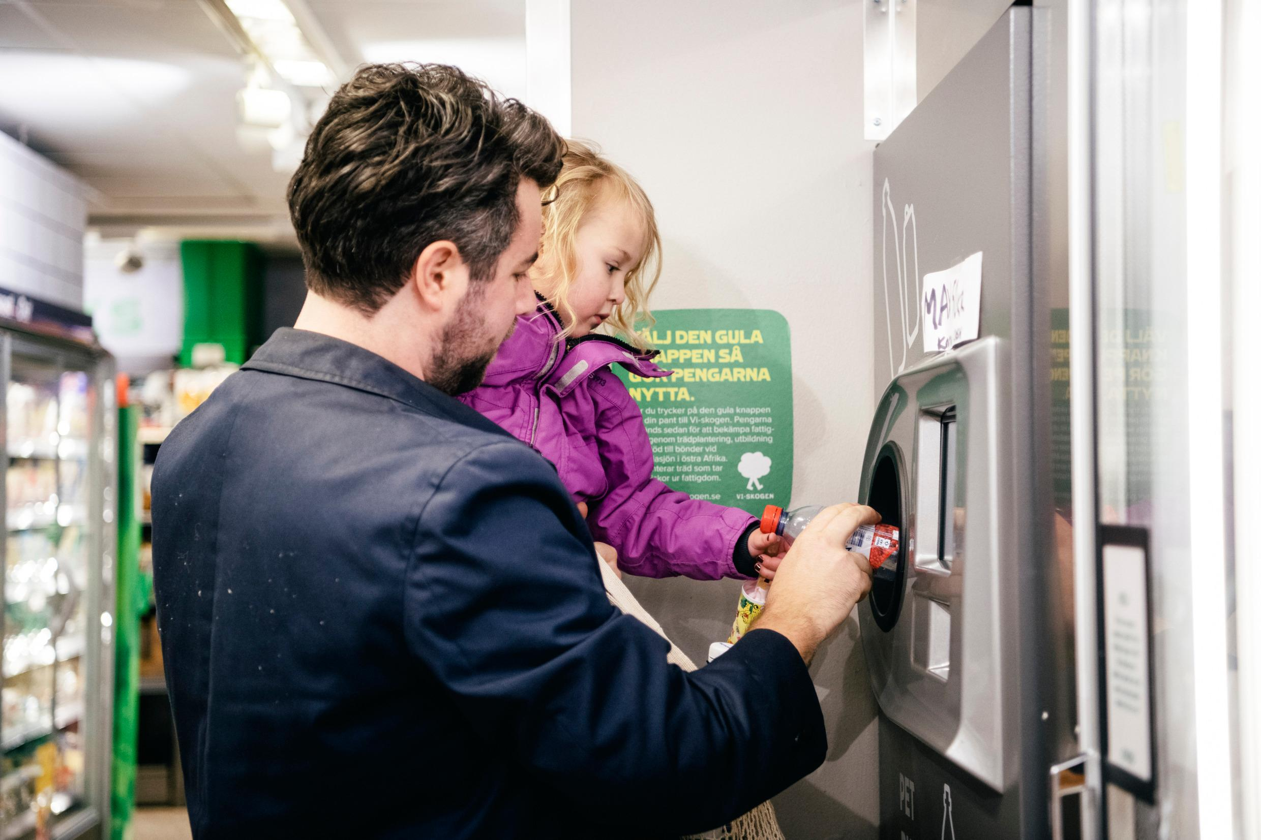 A man is holding a small child. Together they push a plastic bottle into a machine,