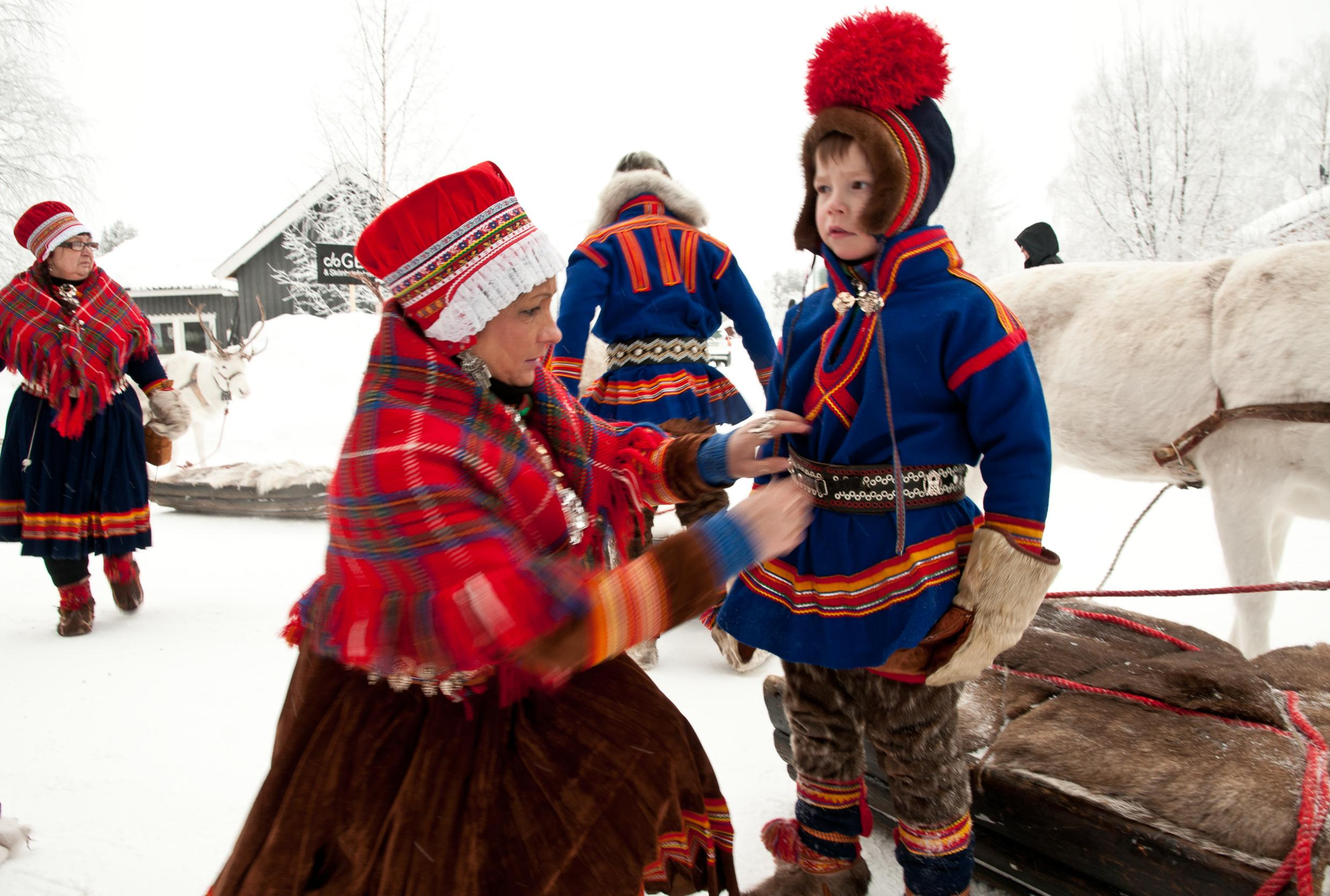 A woman helping a boy dress. They are both wearing traditional Sami clothing. In the background are two more people.