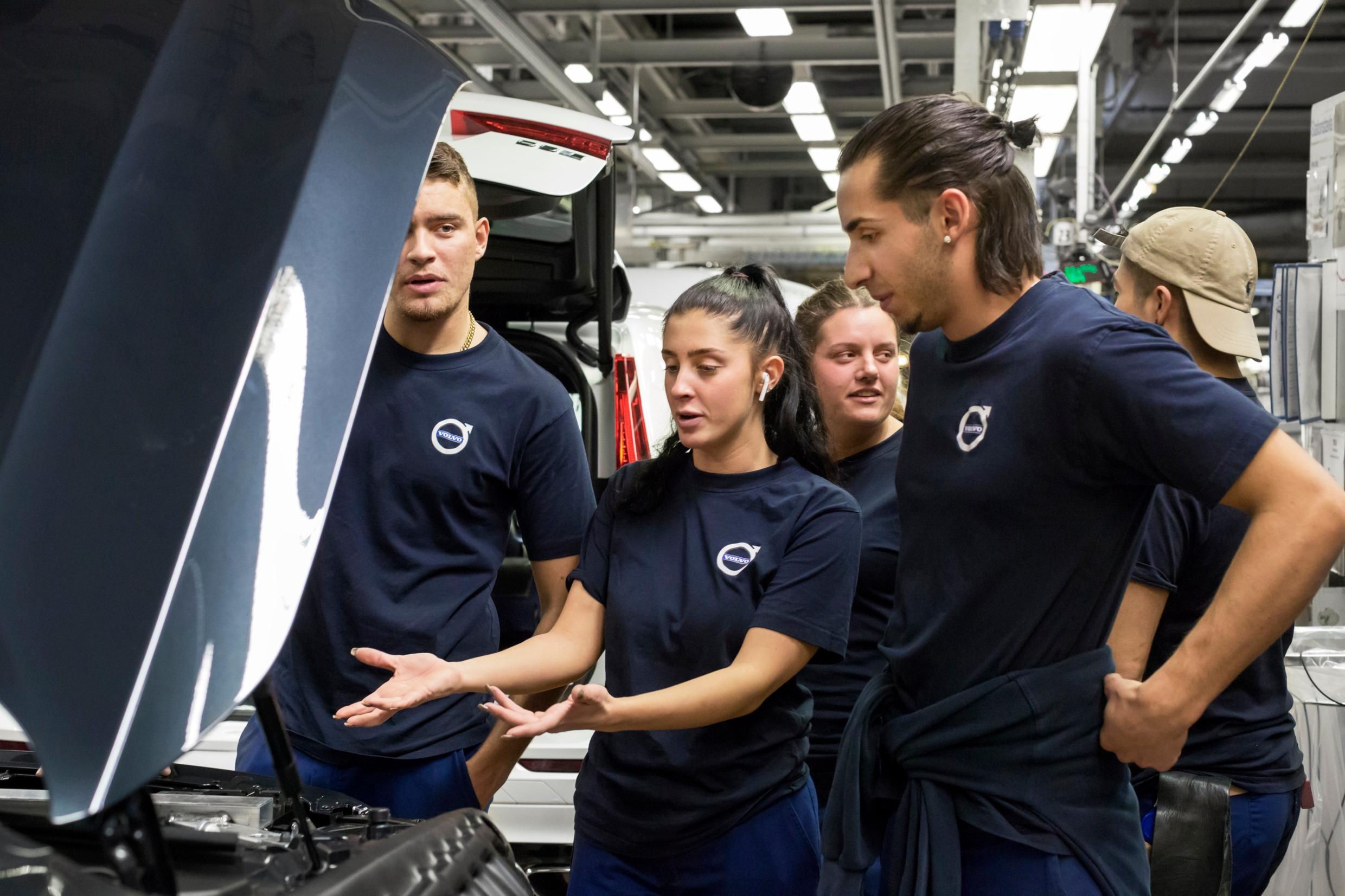 A crowd of workers stand around a car on a factory floor. A woman is gesturing at the engine compartment.