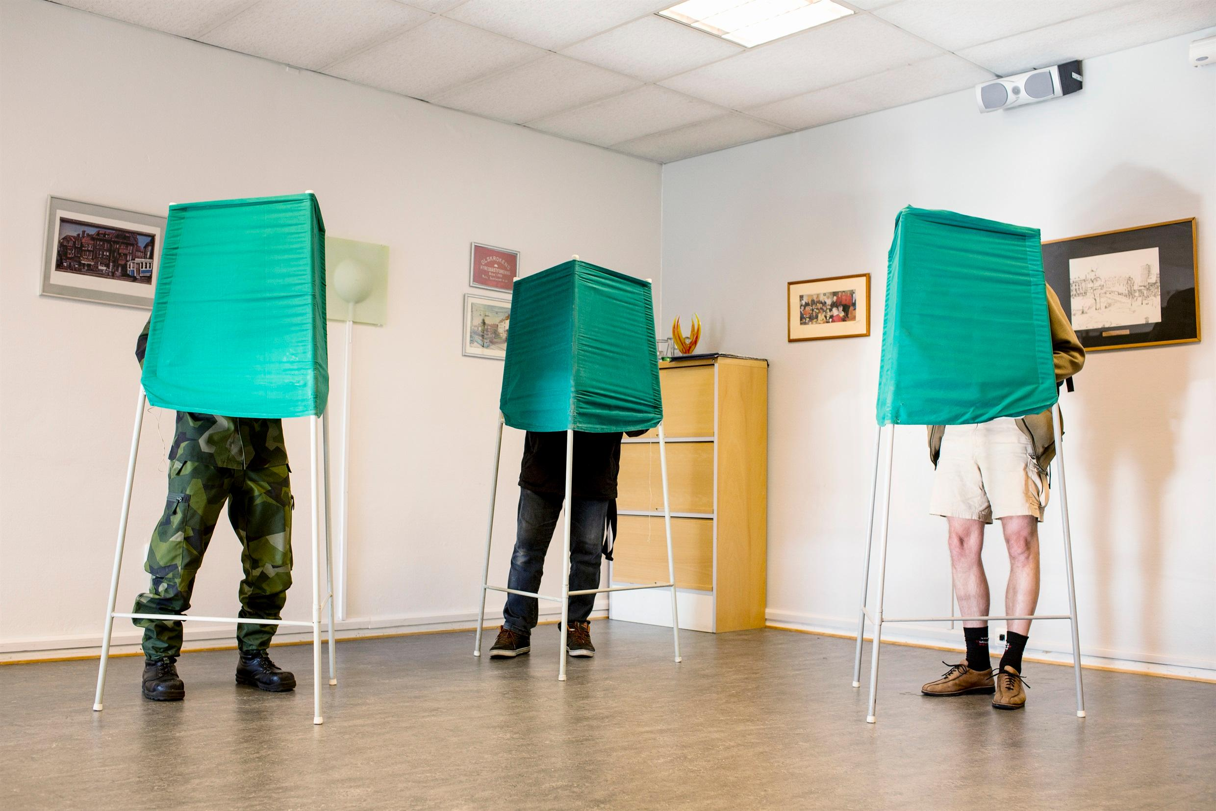 A polling station, where all we can see is three people's legs beneth green screens.