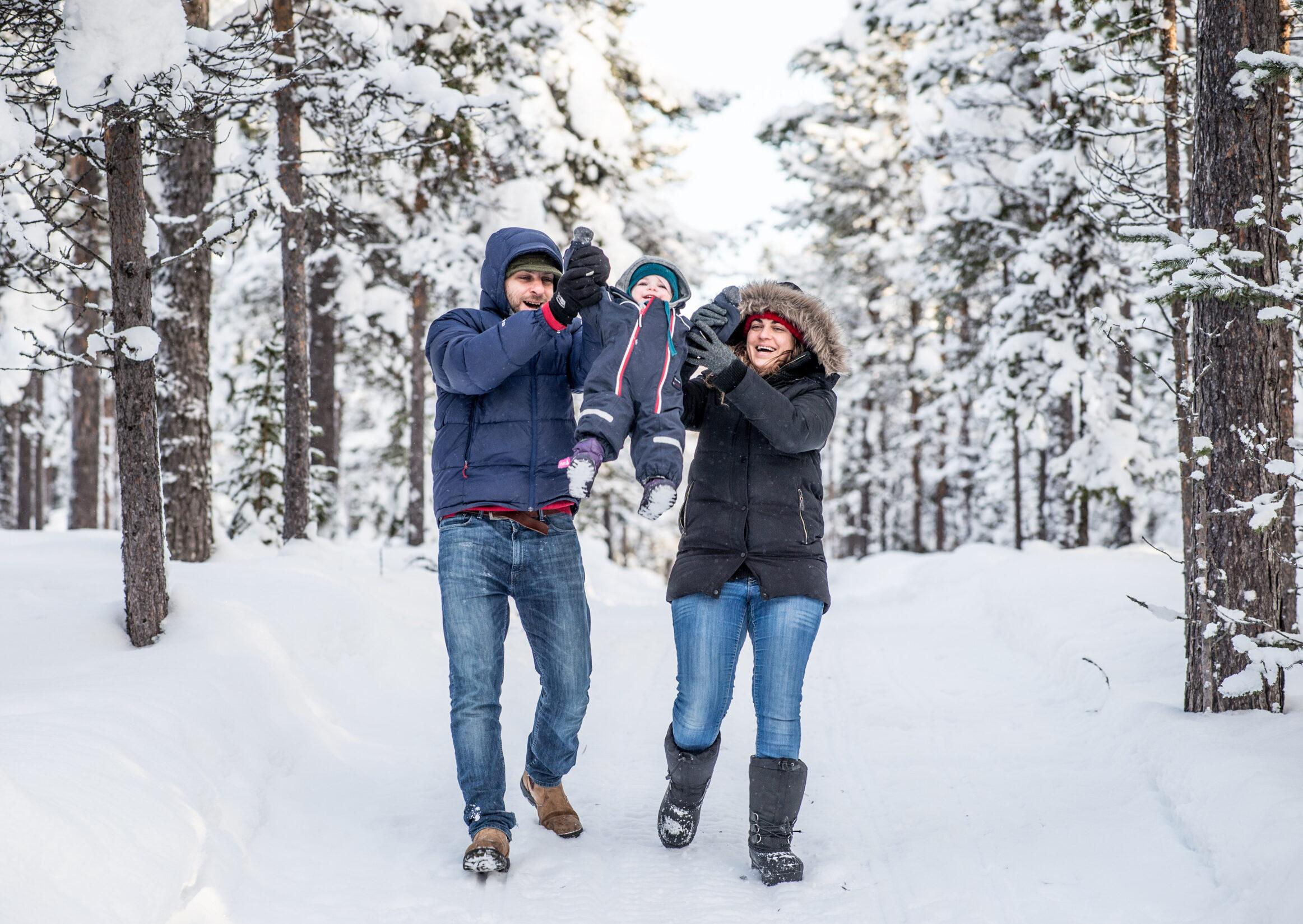 A man and a woman swings a toddler between them in a wintry forest landscape.