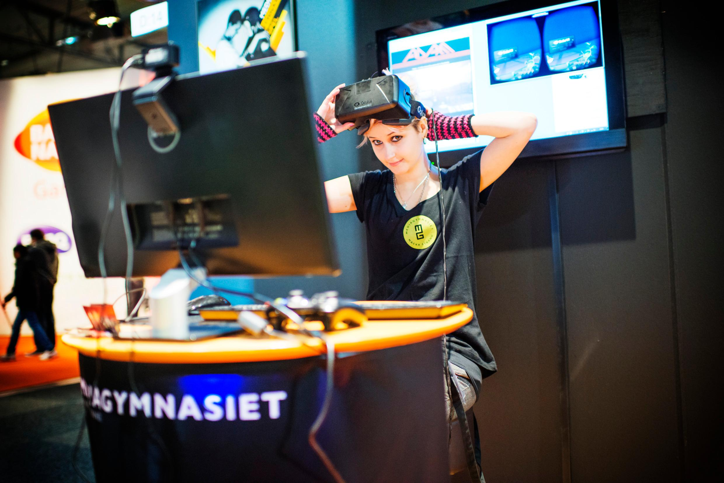 A woman sitting in front of a big computer screen with a VR headset on her head.