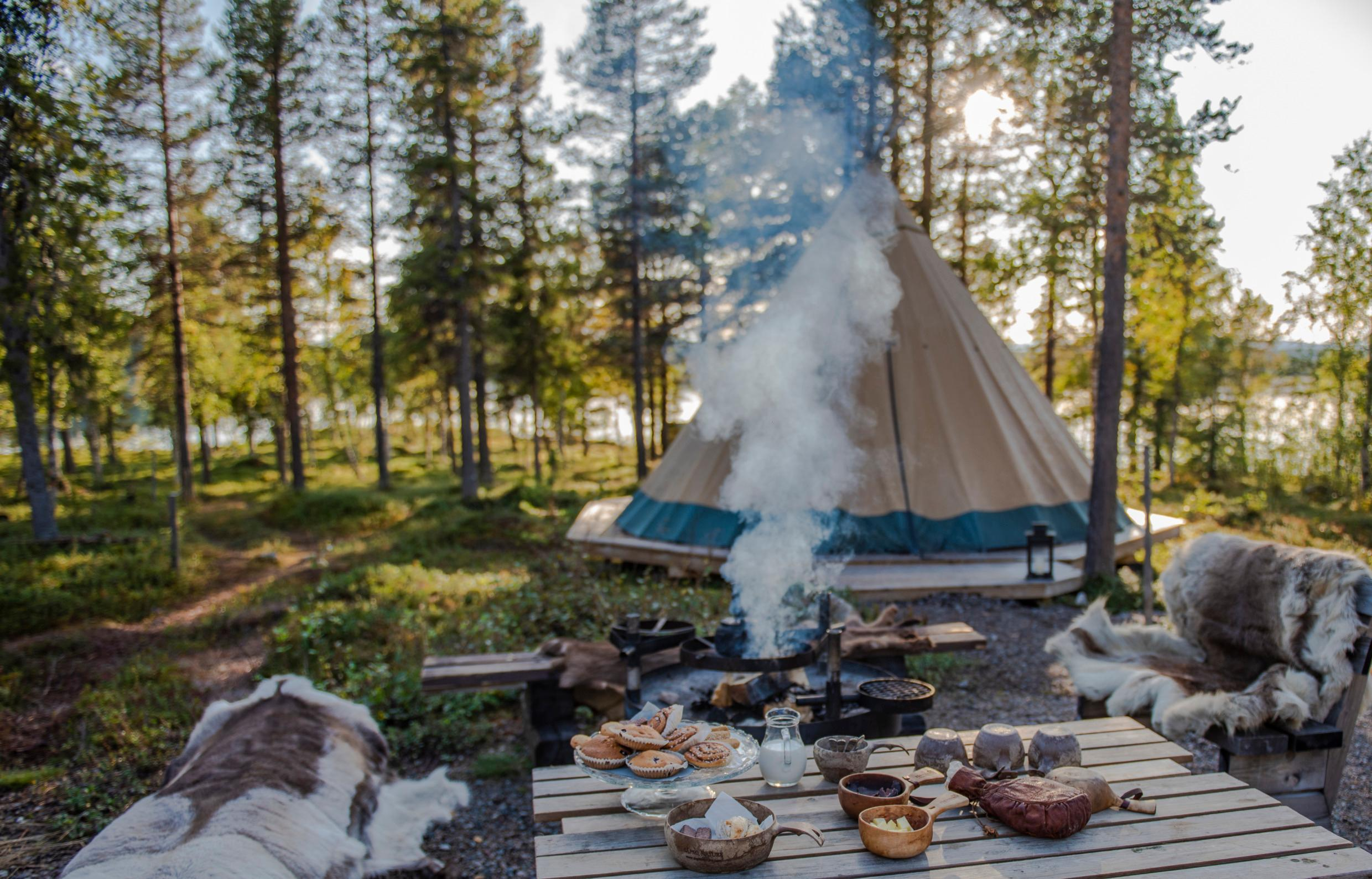 Benches covered in reindeer hides next to a table set with cups and bowls and a plate with buns. A coffee pot is placed over a campfire. A lavvu tent in the background and you get a glimpse of a lake between the trees.